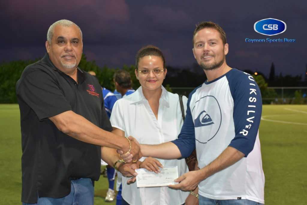 Cabinet Ministers Osbourne Bodden and Tara Rivers present the cheque to Chris Burke of the Hope Foundation.