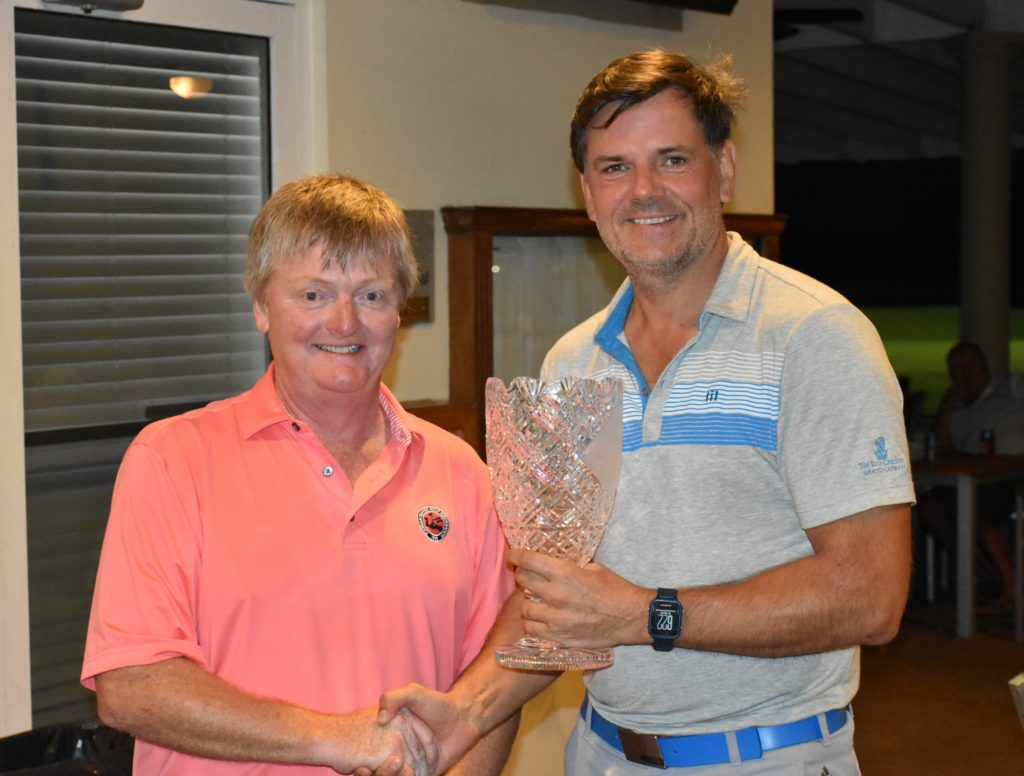 Men's winner Andrew Linford collects his trophy from CIGA President, Paul Woodhouse.