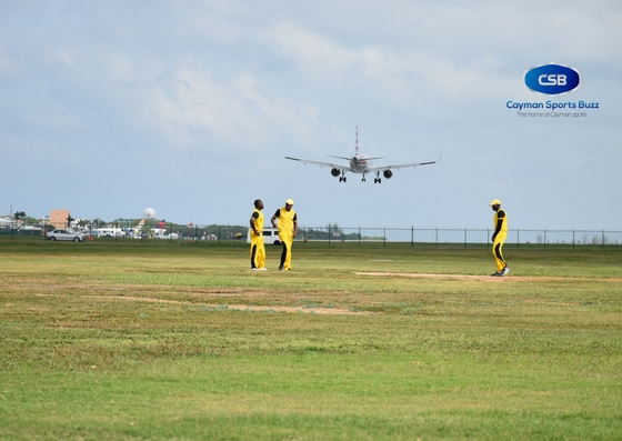 Cricketers ponder their strategy as a plane lands at Owen Roberts International Airport.